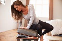 Embalaje de la mujer para las vacaciones que intentan cerrar la maleta llena Fotografía de archivo libre de regalías