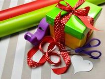 Embalaje del regalo con el papel, las tijeras, la cinta y la etiqueta Fotografía de archivo