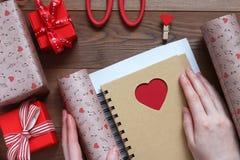 Embalando um caderno com coração no papel do presente ao dia do ` s do Valentim do St Imagem de Stock