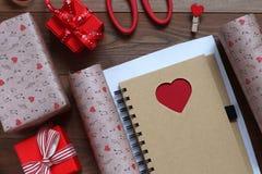 Embalando um caderno com coração no papel do presente ao dia do ` s do Valentim do St Fotos de Stock Royalty Free