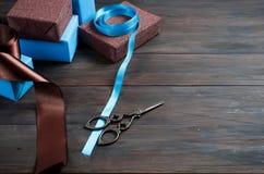 Embalando y adornando los regalos hechos a mano de una Navidad en azul y Br Fotos de archivo