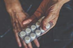 Emballage avec des pilules ou des pilules dans les mains d'une femme agée Photos libres de droits