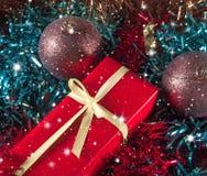 Emballage de cadeau parmi la tresse de Noël, les boules de Noël et les étoiles de scintillement images stock