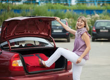 Emballage de femme ses bagages dans le véhicule Image libre de droits