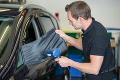 Emballage de voiture enveloppant le miroir latéral avec le film ou l'aluminium de vinyle Photo stock