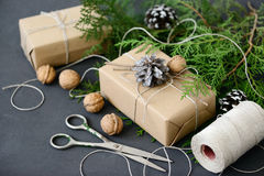 Emballage des cadeaux rustiques de Noël d'eco avec le papier de métier, la ficelle et les branches naturelles de sapin sur le fon Photos stock
