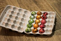 Emballage inachevé des oeufs colorés Vue de c?t? emballage sur un plancher en bois photographie stock libre de droits