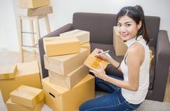 Emballage och flyttning för ung kvinna deras hus, online-förpacka för marknadsföring och leverans, arkivbilder