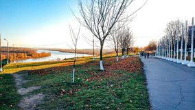The embankment in autumn with trees a road, in the distance the river, fallen leaves on the ground, a bright sunny royalty free stock photography