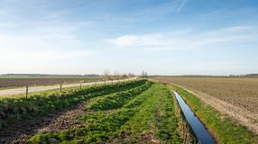 Embankment with country road between plowed fields. Panoramic image of an agricultural area with plowed fields, a ditch and a dike with a country road. The photo Royalty Free Stock Photography