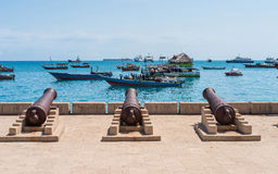 Embankment with guns in Zanzibar Stone Town with ocean on the ba. Embankment with guns in Zanzibar Stone Town with boats in ocean and sky on the background Royalty Free Stock Images
