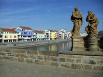 Embankment houses. Colour houses along the river embankment over an old stone bridge with limestone statues, town of Pisek, Czech Republic Royalty Free Stock Images