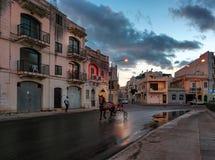 Embankment of the Maltese city of Birzebbuj. Evening. Horseback riding, jumps at sunset. Evening, Malta, clouds, chariot. Embankment of the Maltese city of Royalty Free Stock Photos