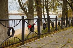 Embankment with a metal fence with locks of love. On an autumn cloudy day stock photos