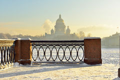 Embankment of the Neva River and St. Isaac's Cathedral in strong frost (focus on the lattice). St. Petersburg, Russia royalty free stock photo