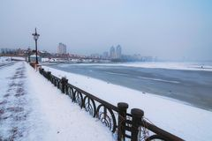 Embankment at the Obolon district in Kyiv, Ukraine. A dangerous hobby - winter fishing. Dnipro River was covered with first thin ice but the lovers of winter Stock Photo