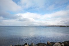 Embankment in Reykjavik over mountains and ocean, dramatic sky. Royalty Free Stock Photo