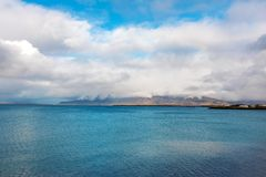 Embankment in Reykjavik over mountains and ocean, dramatic sky. Stock Photo