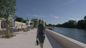 The embankment of the River Seine in Paris - a woman walking along the embankment - is removed from the back. Paris. France. stock video footage