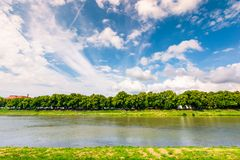 Embankment of the river Uzh. Beautiful summer scenery. longest european linden alley under the gorgeous cloudscape on a blue sky royalty free stock photo