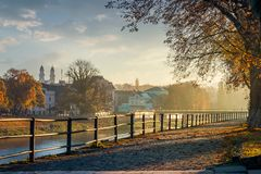 Embankment of the river Uzh. Beautiful urban scenery with colorful foliage on trees in morning haze. bridge, theater, cathedral towers and other landmarks of stock image