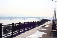Embankment of the river. The Yenisei River. Benches along the sidewalk. Black patterned fence along the waterfront. On the horizon Stock Photo