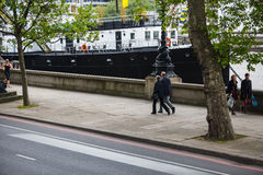 Embankment. Two people walk along the bank of the river Thames in London, England stock photo