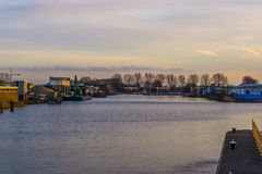Embankment with water view in the city of Alphen aan den rijn, The Netherlands, industrial zone with buildings. A Embankment with water view in the city of royalty free stock photo