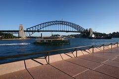 Embankment waterfront promenade with ferry cruising by iconic Sydney Harbor Bridge. Coastal cityscape with historic landmark. Boardwalk along urban coast with royalty free stock photography