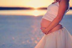 Embarazada en la puesta del sol Fotos de archivo