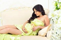 Embarazada en vestido verde claro blando en un sofá con los lirios Fotos de archivo