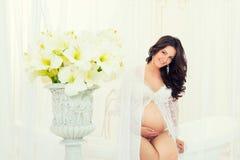 Embarazada hermoso en bata de casa blanca ligera del cordón en el cuarto de baño Fotografía de archivo