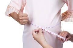 Embarazada midiendo su sentir bien de la pizca de la cintura Fotografía de archivo libre de regalías