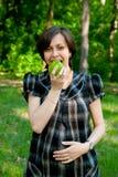 Embarazado con una manzana imagenes de archivo