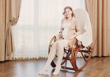 Embarazo feliz que se sienta en mecedora Imágenes de archivo libres de regalías