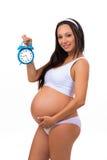 Embarazo feliz Reloj de alarma sonriente de la explotación agrícola de la mujer embarazada Foto de archivo