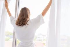 Embarazo, maternidad, gente y concepto de la expectativa - cercano para arriba de las cortinas de ventana felices de abertura de  imagen de archivo