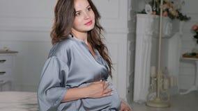 Embarazo, resto, gente y concepto de la expectativa - mujer embarazada feliz que se sienta en cama y que toca su vientre en casa almacen de video