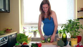 Embarazo y nutrición La mujer embarazada cortó verduras de la paprika en la tabla de cocina