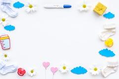 Embarazo y preparación para el parto Prueba de embarazo cerca de botines y accesorios del niño en la opinión superior del fondo b Imagen de archivo libre de regalías