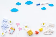 Embarazo y preparación para el parto Prueba de embarazo cerca de botines y accesorios del niño en la opinión superior del fondo b Imágenes de archivo libres de regalías