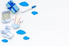 Embarazo y preparación para el parto Prueba de embarazo cerca de los accesorios del niño en el espacio blanco de la copia de la o Imagen de archivo libre de regalías