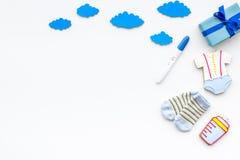 Embarazo y preparación para el parto Prueba de embarazo cerca de los accesorios del niño en el espacio blanco de la copia de la o Fotografía de archivo