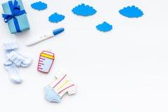 Embarazo y preparación para el parto Prueba de embarazo cerca de los accesorios del niño en el espacio blanco de la copia de la o Foto de archivo