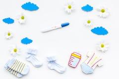 Embarazo y preparación para el parto Prueba de embarazo cerca de los accesorios del niño en la opinión superior del fondo blanco Imagenes de archivo