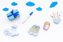 Embarazo y preparación para el parto Prueba de embarazo cerca de los accesorios del niño en la opinión superior del fondo blanco Imagen de archivo libre de regalías