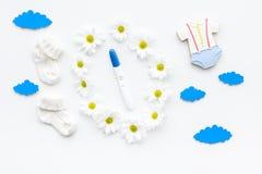 Embarazo y preparación para el parto Prueba de embarazo cerca de los accesorios del niño en la opinión superior del fondo blanco Foto de archivo