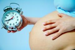 Embarazo y reloj Imagen de archivo libre de regalías
