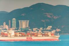 A embarcação da empresa de transporte da carga carregou com os bens dos navios de recipientes através do canal de Lamma em Hong K imagem de stock