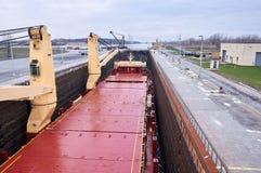 Embarcação do navio mercante com os dois guindastes que passam fechamentos nos grandes lagos, Canadá no tempo de inverno Fotografia de Stock